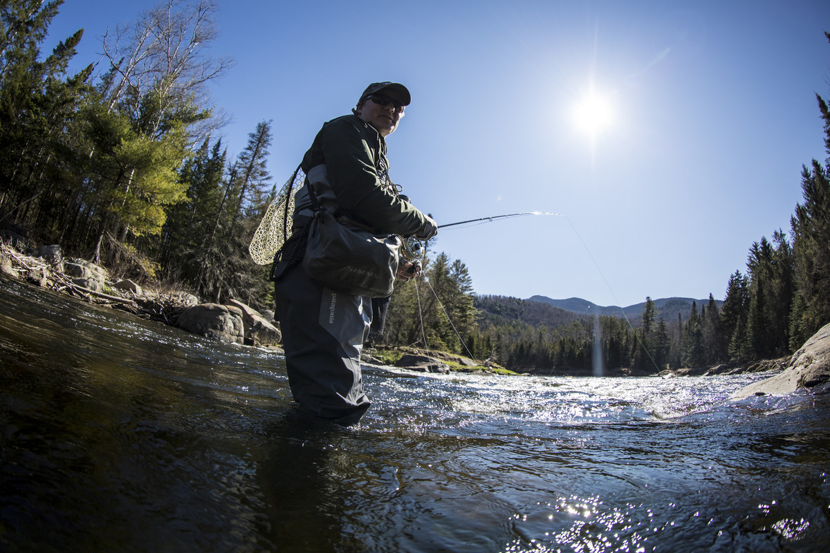 To be good at something, you must learn. Why not speed up the process? (image shows an angler in waders, outfitted with fly fishing equipment, mid-river)