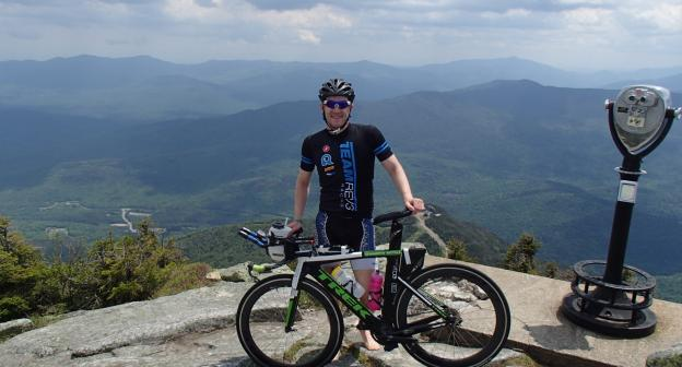 A cyclist in a pink jersey takes a selfie while biking along Route 9N