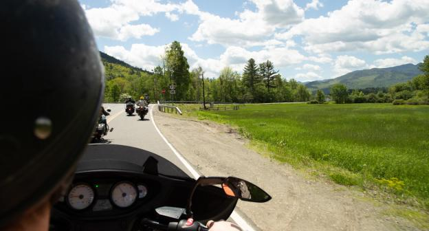 A red motorcyle sits in front of the steep backdrop of Whiteface Mountain in summer.