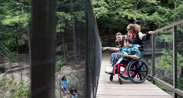 A woman in a wheelchair views the falls of High Falls Gorge from an accessible bridge.
