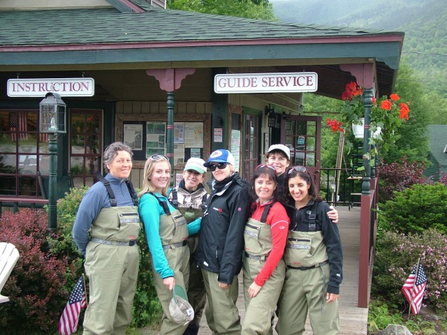 A group of women on a fly fishing trip pose at the Hungry Trout Fly Shop