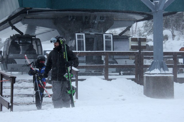 Skiers exit the gondola on the summit of Little Whiteface.