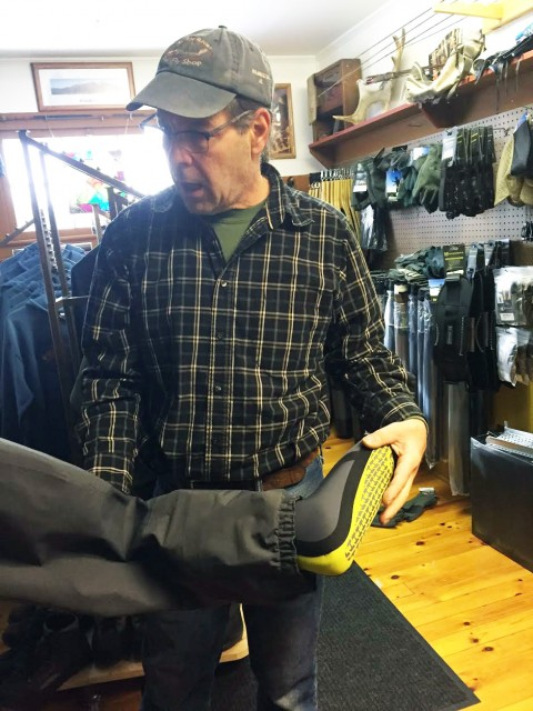 Tom explaining the neoprene booties attached to men and women fly fishing waders